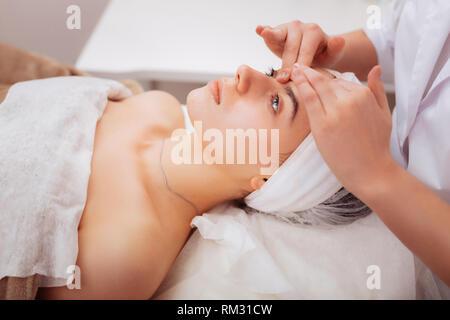 Nice pleasant young woman enjoying head massage - Stock Photo