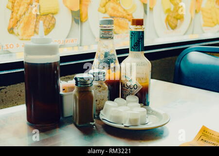 Waikiki, Hawaii - 25 May, 2016: Common condiments and milk on a table at a diner in downtown Waikiki. - Stock Photo