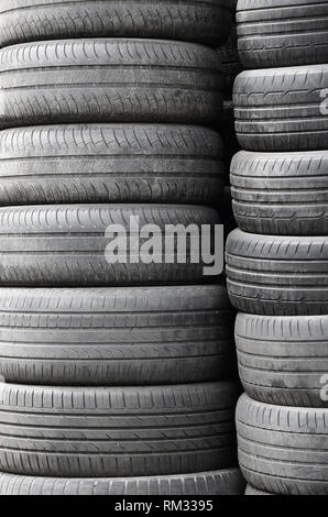 Old used tires stacked with high piles in secondary car parts shop garage close up - Stock Photo
