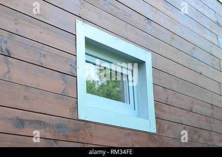 Plastic PVC window in modern passive wooden house facade wall. PVC windows are the number one in house energy efficiency - Stock Photo