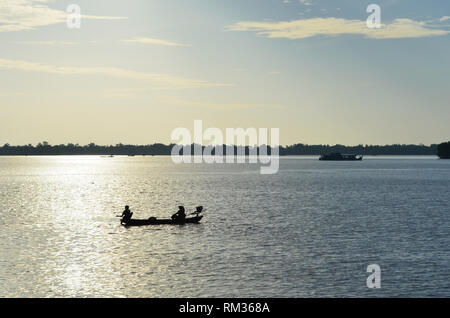 Two fishermen are in a small boat with an outboard motor. They are silhouetted against the late afternoon sun. A few other boats are on the river. The - Stock Photo