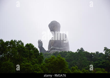 The enormous Tian Tan Buddha statue in the middle of the fog up on high mountain near Po Lin Monastery, Lantau Island, Hong Kong - Stock Photo