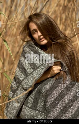 Young woman in undergrowth, wrapped in towel. Crete, Greece. - Stock Photo