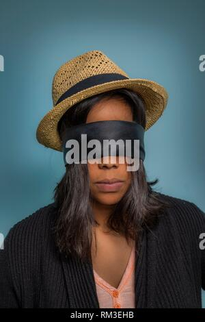 Young Hispanic woman wearing a blindfold and a straw hat. - Stock Photo