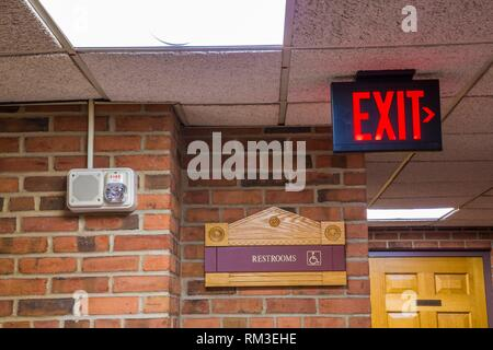 '''Exit'' and ''Restrooms'' signs on brick walls in an office hallway. - Stock Photo