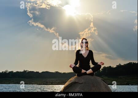young woman practising yoga posture by the Senanayake Samudraya Lake, Gal Oya National Park, Sri Lanka, Indian subcontinent, South Asia. - Stock Photo