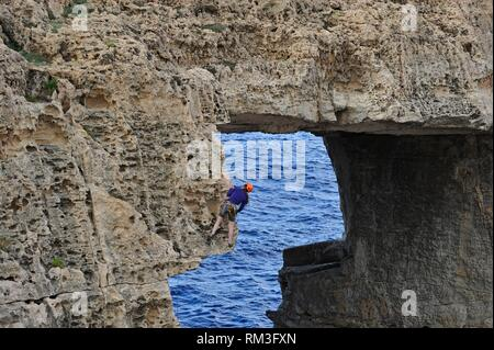 climbers at Wied Il-Mielah a limestone natural arch on the northwest coast of Gozo Island, Malta, Mediterranean Sea, Southern Europe. - Stock Photo