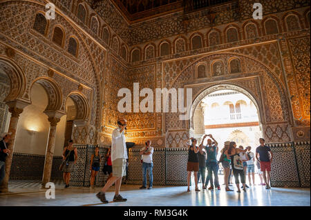 Tourists in the Ambassador's Hall (Salon De Embajadores), also known as the Throne Room in the Mudejar palace of the Alcazar in Seville, a royal palac - Stock Photo