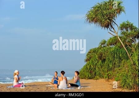 yoga class on the beach by Sen Wellness Sanctuary, near Tangalle, South Coast of Sri Lanka, Indian subcontinent, South Asia. - Stock Photo