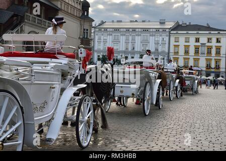 tourist horse-drawn carriages on the Main Market Square (Rynek Glowny) in the Old Town, Krakow, Malopolska Province (Lesser Poland), Poland, Central - Stock Photo