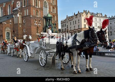 tourist horse-drawn carriages in front of the St. Mary´s Basilica on the Main Market Square (Rynek Glowny) in the Old Town, Krakow, Malopolska - Stock Photo
