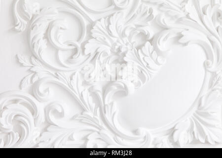Beautiful ornate white decorative plaster mouldings in studio. The white wall is decorated with exquisite elements of plaster stucco - Stock Photo