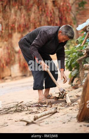 Elderly man cutting firewood for the kitchen,Yunnan Province, China - Stock Photo