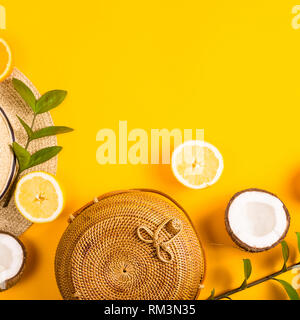 Summer bright yellow background with a straw bag, hat, oranges, lemon, coconut and a green branch. Top view, flat lay - Stock Photo