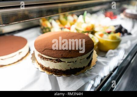 Tiramisu cake. Showcase desserts in an Italian cafe or trattoria. Variety of cakes on display. - Stock Photo