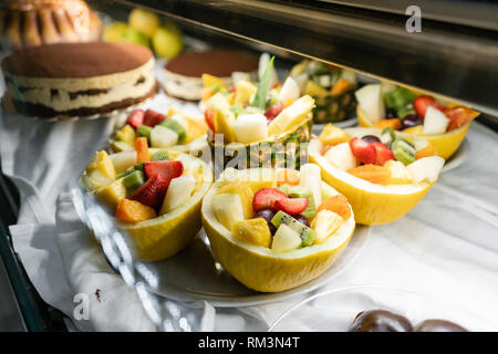 Dessert of fresh fruit.. Showcase desserts in an Italian cafe or trattoria. Variety of cakes on display. - Stock Photo