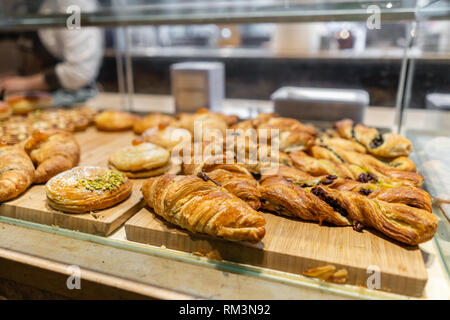 Croissant, puffs and other pastries. Showcase desserts in an Italian cafe or trattoria. Variety of cakes on display. - Stock Photo
