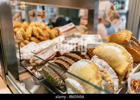 Buns, pies, biscuits and other pastries. Showcase desserts in an Italian cafe or trattoria. Variety of cakes on display. - Stock Photo