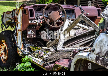 A decrepit Nissan SUV and miscellaneous wooden debris, Kauai, Hawaii - Stock Photo