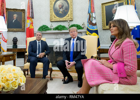 Washington DC, USA. 13th Feb, 2019. US President Donald J. Trump (C) and President of Colombia Ivan Duque (L) meet beside US First Lady Melania Trump (R) in the Oval Office of the White House in Washington, DC, USA, 13 February 2019. President Trump and President Duque are meeting to discuss economic policies, combatting narcotics and the current situation in Venezuela. Credit: Michael Reynolds/Pool via CNP /MediaPunch Credit: MediaPunch Inc/Alamy Live News - Stock Photo