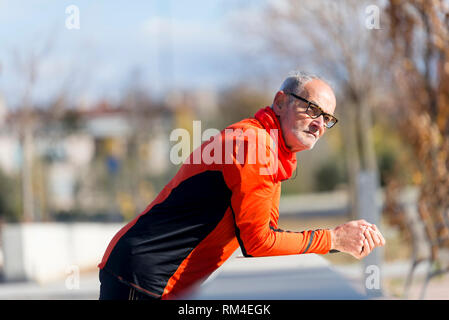 Athletic senior male leaning on fence - Stock Photo