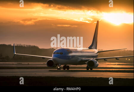Aeroplane belong to the TUI UK Group waiting on the runway at Gatwick Airport in the UK, at dusk. - Stock Photo