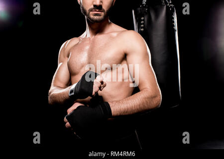 cropped view of shortless athlete wrapping up gloves on black background - Stock Photo