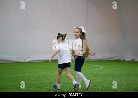 Two little girls going across the football field holding each other's hands, one of them looking directly at the camera - Stock Photo