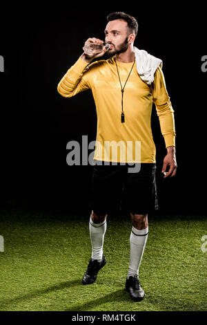 bearded referee drinking water from bottle and standing with towel on shoulder isolated on black - Stock Photo