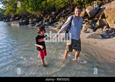Bodhi Garrett and son Vajra walk the beach of MU KO SURIN ISLAND - MU KO SURIN NATIONAL PARK, THAILAND - Stock Photo