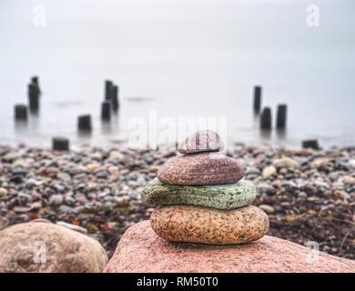 Stones pyramid symbolizing zen, harmony, balance on ocean background. - Stock Photo