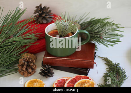 Warm composition on the table, a red scarf, dried oranges, heart-shaped cookies, a cup of hot tea with a slice of grapefruit and pine branches - Stock Photo