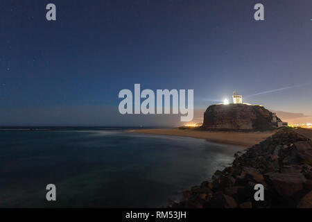 An illuminated noght view of Nobbys Lighthouse - Newcastle NSW Australia. This lighthouse at the mouth of the Hunter River is a prominent landmark in  - Stock Photo