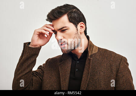 Portrait of stylish dark-haired man wearing brown jacket, touching his forehead and looking away isolated over white background. Stress concept. - Stock Photo