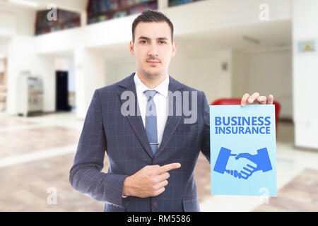 Trustworthy person advertising business insurance by pointing with index finger to blue paper containing text and hand-shake symbol as deal concept - Stock Photo