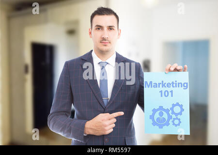 Man wearing suit and tie showing marketing must-know with mechanism and person drawing on blue paper as learning concept - Stock Photo