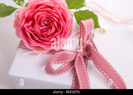 Luxury bouquet made of red roses in flower shop and white ribbon on wooden board. Overhead top view, flat lay. Copy space. - Stock Photo