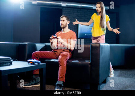 Young woman angry at her boyfriend playing video games with gaming console sitting on the couch at home or playing club - Stock Photo