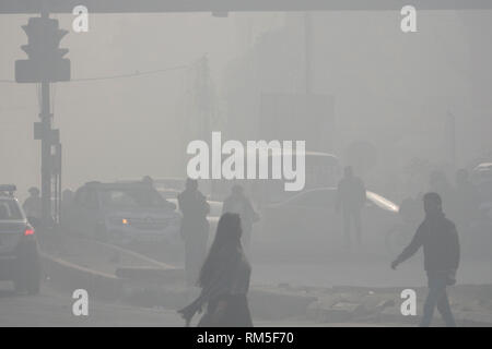 Pedestrians walking in hazardous levels of air pollution in Delhi Aerocity, New Delhi, India - Stock Photo