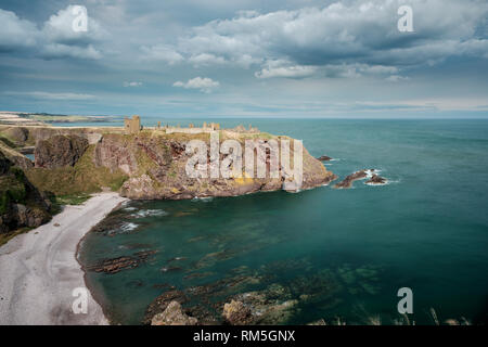 Dunnottar castle ruin and the surrounding coastline, bathed in sunshine with clouds overhead, Stonehaven, Aberdeenshire, Scotland - Stock Photo