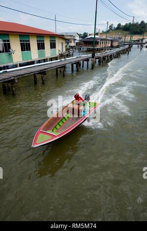 Speedboat water taxi, passing walkway and shacks on stilts in Brunei River, Water Village (Kampong Ayer), Bandar Seri Begawan, Brunei - Stock Photo