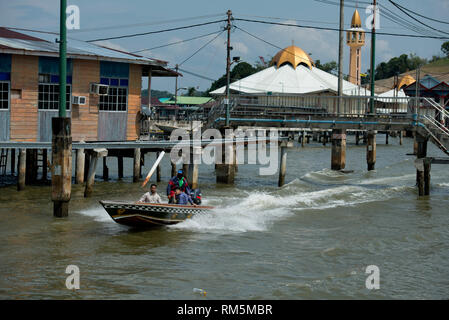 Speedboat water taxi, passing walkway and shacks on stilts in Brunei River with mosque in background, Water Village (Kampong Ayer), Bandar Seri Begawa - Stock Photo