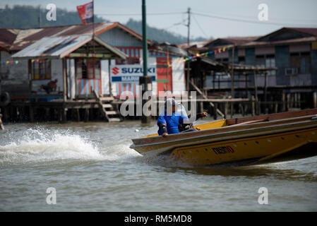 Speedboat water taxi, passing shacks on stilts in river, Water Village (Kampong Ayer), Bandar Seri Begawan, Brunei - Stock Photo