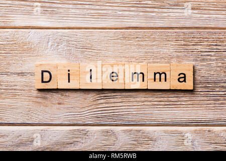 Dilemma word written on wood block. Dilemma text on wooden table for your desing, concept. - Stock Photo