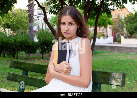 Upset girl is sitting on the bench and holding a book in the park. - Stock Photo