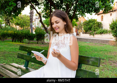 Cute girl is holding a pen, a notepad and crumpled paper sitting on the bench outside. - Stock Photo