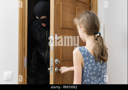 Little girl opening the door to the robber. - Stock Photo