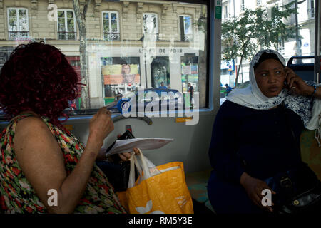 Headscarved black African woman. Women travelling on bus, window and view of boulevard Barbès, 75018 Paris, France - Stock Photo