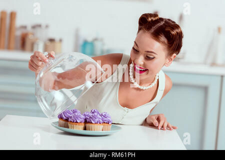 Pretty pin up girl looking at plate full of homemade cupcakes - Stock Photo