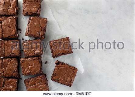 Chocolate brownie on paper on white marble top view flat lay looking down - Stock Photo